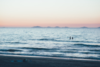 Distant people waist deep in ocean, Sorso, Sassari, Italy