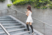 Woman ascending steps using digital tablet