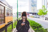 Woman texting on smartphone in urban area, Milan, Italy