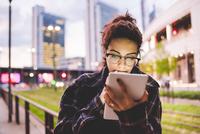 Woman in urban area using digital tablet, Milan, Italy