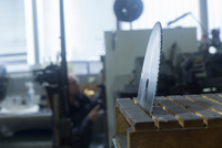 Rotary blade in holder, man working in background