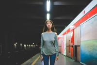 Portrait of young woman standing staring on railway platform at night 11015296260| 写真素材・ストックフォト・画像・イラスト素材|アマナイメージズ