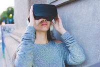 Young woman on sidewalk using virtual reality headset