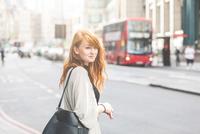 Young woman crossing street, London, UK