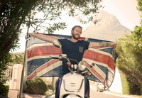 Man holding up union jack sitting on moped, Cape Town, South Africa