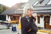 Woman drinking coffee outside hotel, Sattelbergalm, Tirol, Austria
