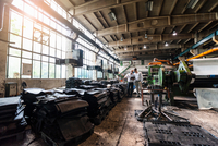 Colleagues inspecting rubber in tyre manufacturing plant, Ballenstedt, Germany