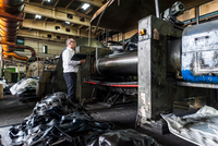 Man inspecting manufacturing machinery in tyre plant, Ballenstedt, Germany