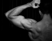 Rear view of bare-chested man flexing bicep muscles