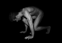 Nude muscular man crouching