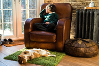 Boy relaxing on arm chair after school 11015296619| 写真素材・ストックフォト・画像・イラスト素材|アマナイメージズ