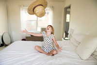 Young girl sitting on bed, throwing straw hat up in air 11015296633| 写真素材・ストックフォト・画像・イラスト素材|アマナイメージズ