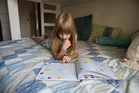 Young girl laying on bed reading book
