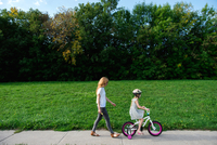 Young girl riding her bicycle followed by mother