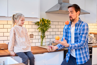 Mid adult man juggling fruit for daughter in kitchen 11015296641| 写真素材・ストックフォト・画像・イラスト素材|アマナイメージズ