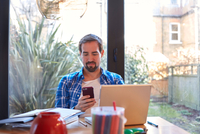 Mid adult man reading smartphone text at dining table