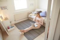Mid adult woman sitting on living room floor using laptop 11015296654| 写真素材・ストックフォト・画像・イラスト素材|アマナイメージズ