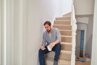 Mid adult man sitting on staircase reading smartphone texts