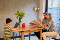 Mid adult couple looking at paperwork on dining table whilst son uses laptop 11015296690| 写真素材・ストックフォト・画像・イラスト素材|アマナイメージズ