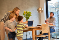 Mid adult woman and sons looking at laptop on dining table 11015296691| 写真素材・ストックフォト・画像・イラスト素材|アマナイメージズ