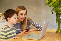 Mid adult woman and son looking at laptop on dining table 11015296692| 写真素材・ストックフォト・画像・イラスト素材|アマナイメージズ