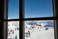 Window view of crowds of ski tourists on mountainside, Zugspitze, Bayern, Germany