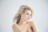 Studio portrait of beautiful blond bare shouldered young woman