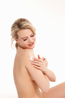 Studio shot of beautiful naked blond young woman applying moisturiser to shoulder