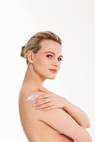 Studio portrait of beautiful naked blond young woman applying moisturiser to shoulder