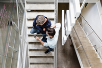 Colleagues on stairway looking at smartphone