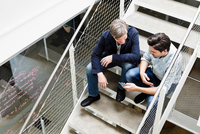 Colleagues sitting on stairway looking at smartphone