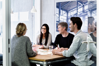 Colleagues at meeting in conference room smiling