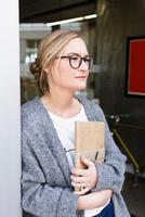 Woman holding digital tablet looking away