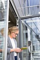 Woman in doorway using digital tablet