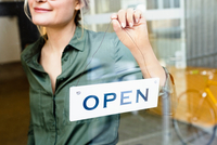 Woman placing open sign on glass door