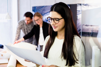 Young woman in office holding paperwork smiling