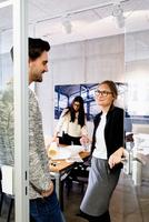 Colleagues in office doorway chatting