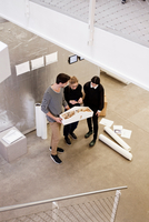 Architects in office looking at architectural model