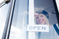 Woman placing open sign on glass door smiling