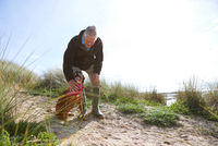 Man stroking pet dog on sand dunes, Constantine Bay, Cornwall, UK