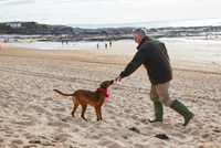 Man and dog on beach, Constantine Bay, Cornwall, UK