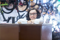 Woman at counter in bicycle shop looking at camera smiling