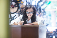 Woman working at counter in bicycle shop