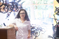Woman in bicycle shop leaning against counter, looking at camera smiling