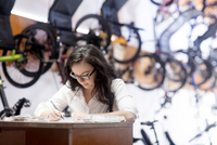 Woman in bicycle shop working at counter