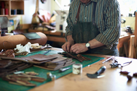 Male worker in leather workshop, arranging leather, mid section