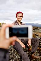 Hikers taking photograph on cliff top, Keimiotunturi, Lapland, Finland