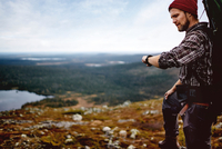 Hiker checking time on cliff top, Keimiotunturi, Lapland, Finland