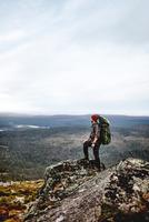 Hiker enjoying view on cliff top, Keimiotunturi, Lapland, Finland