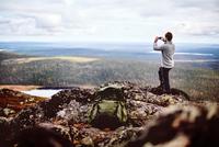 Hiker taking photograph on cliff top, Keimiotunturi, Lapland, Finland